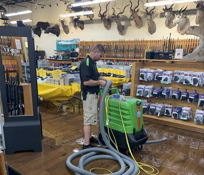 Hunting Gun Range Store flooded floor, man with green equipment and hose, mounts on wall