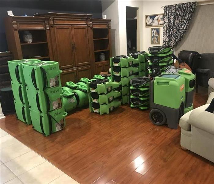 living room stacked with green drying equipment--staging area