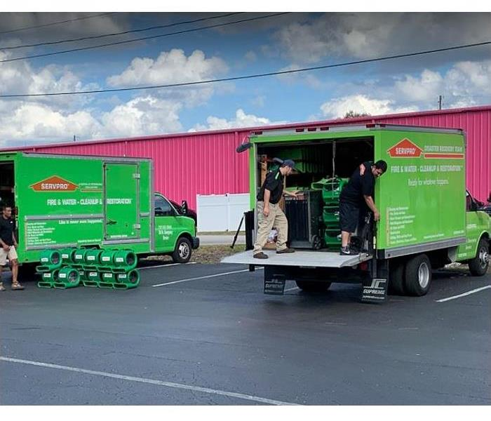 SERVPRO technicians loading V=vehicles in the Green Fleet with restoration equipment
